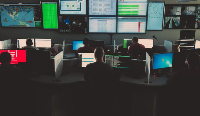 A room full of Hivelocity employees at desks surrounded by computer monitors