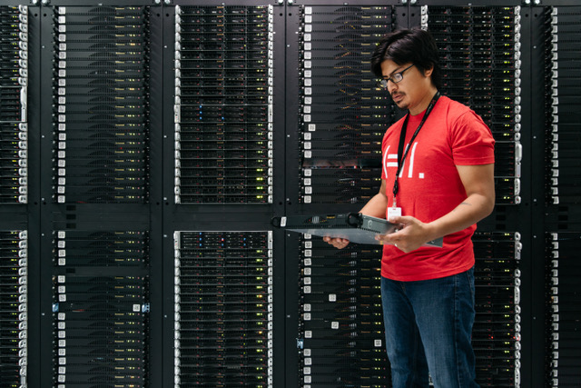 A Hivelocity employee standing next to a cabinet of servers