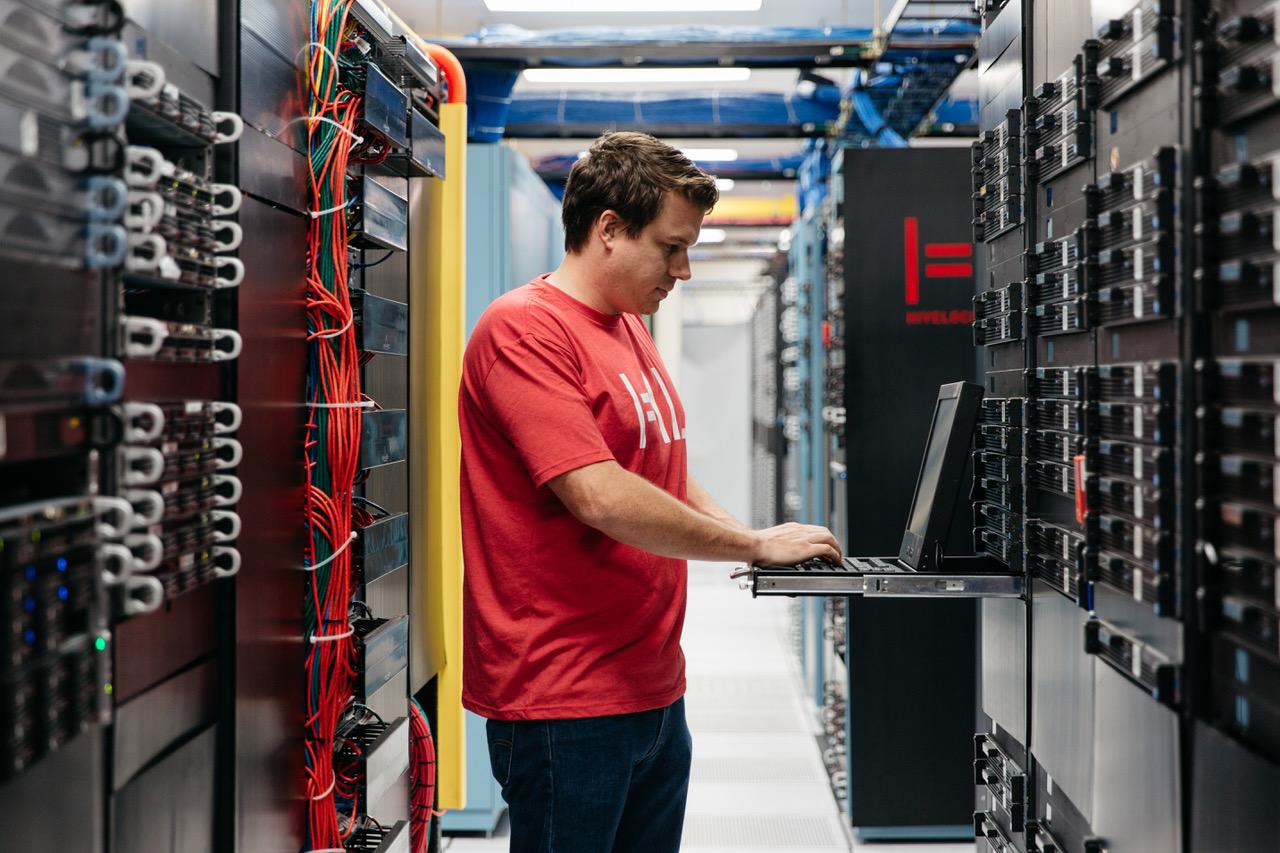A Hivelocity employee standing among racks of servers