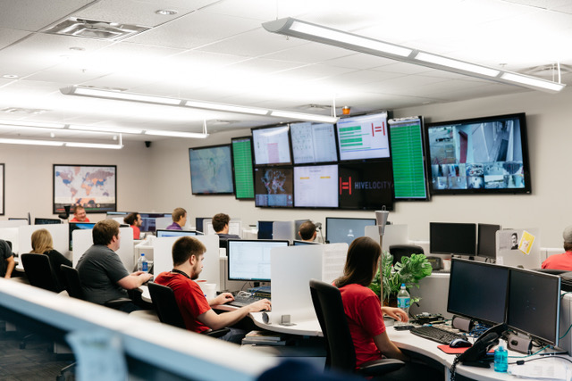 A group of Hivelocity employees sitting at desks in a room filled with monitors