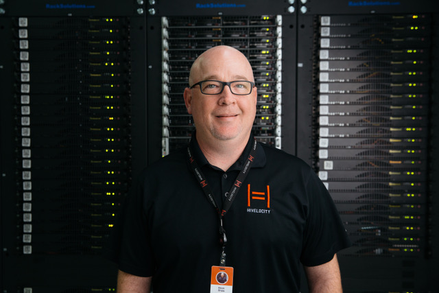 A Hivelocity employee standing in front of several racks of servers