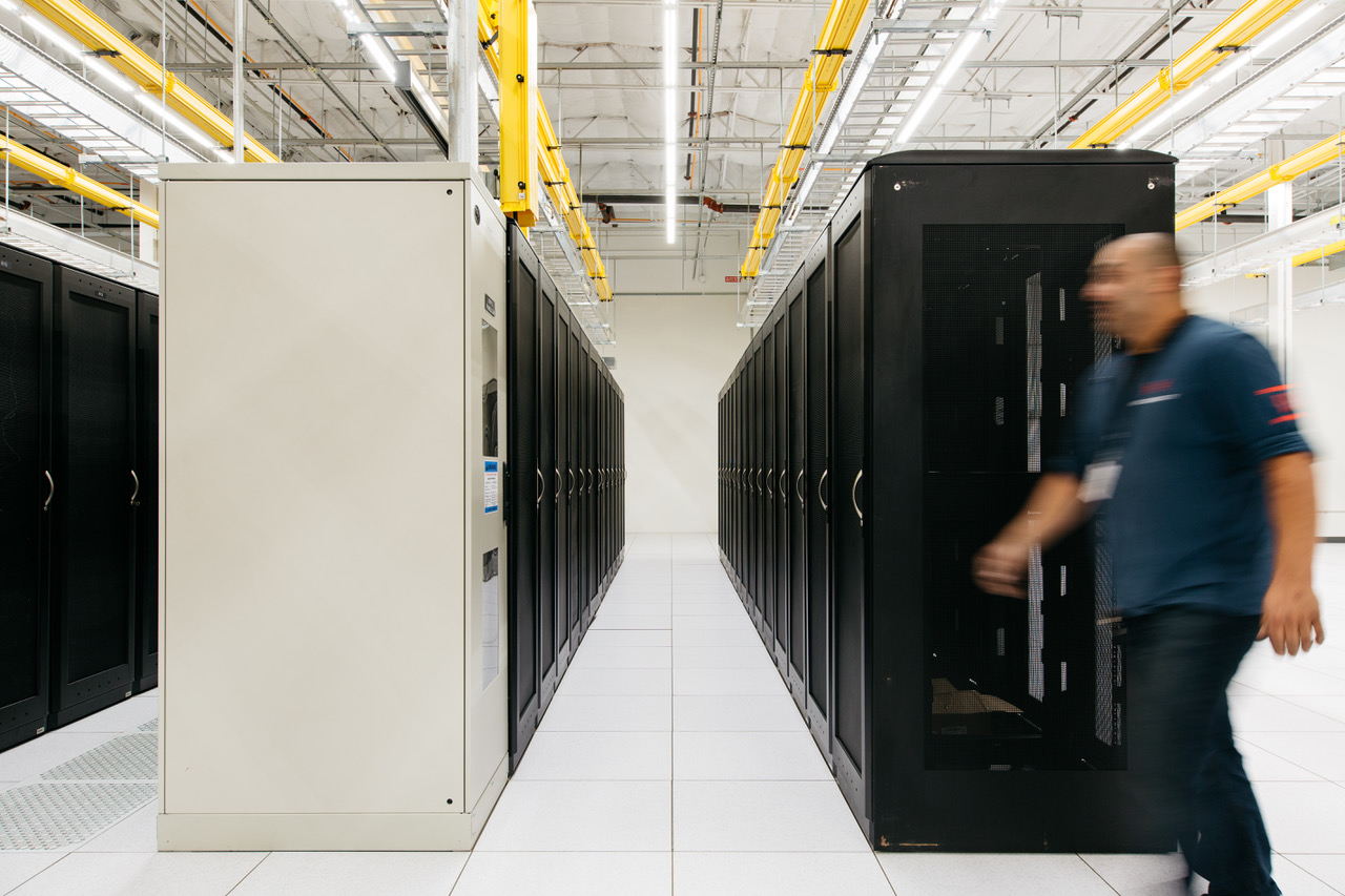 A Hivelocity employee walking past a row of server cabinets within one of our data centers
