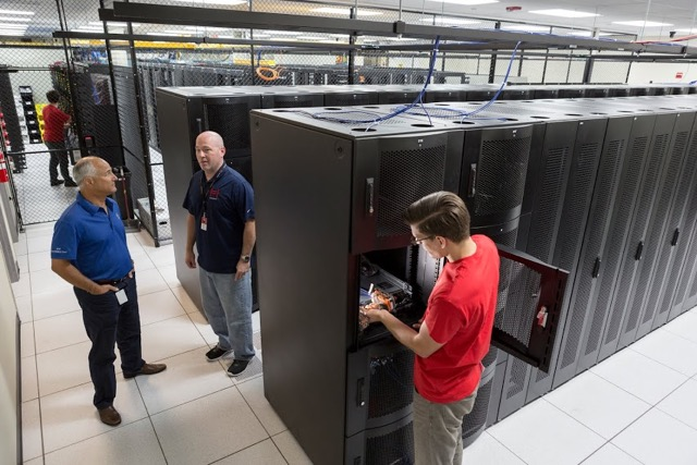Hivelocity employee working on a server in our data center as two customers stand by