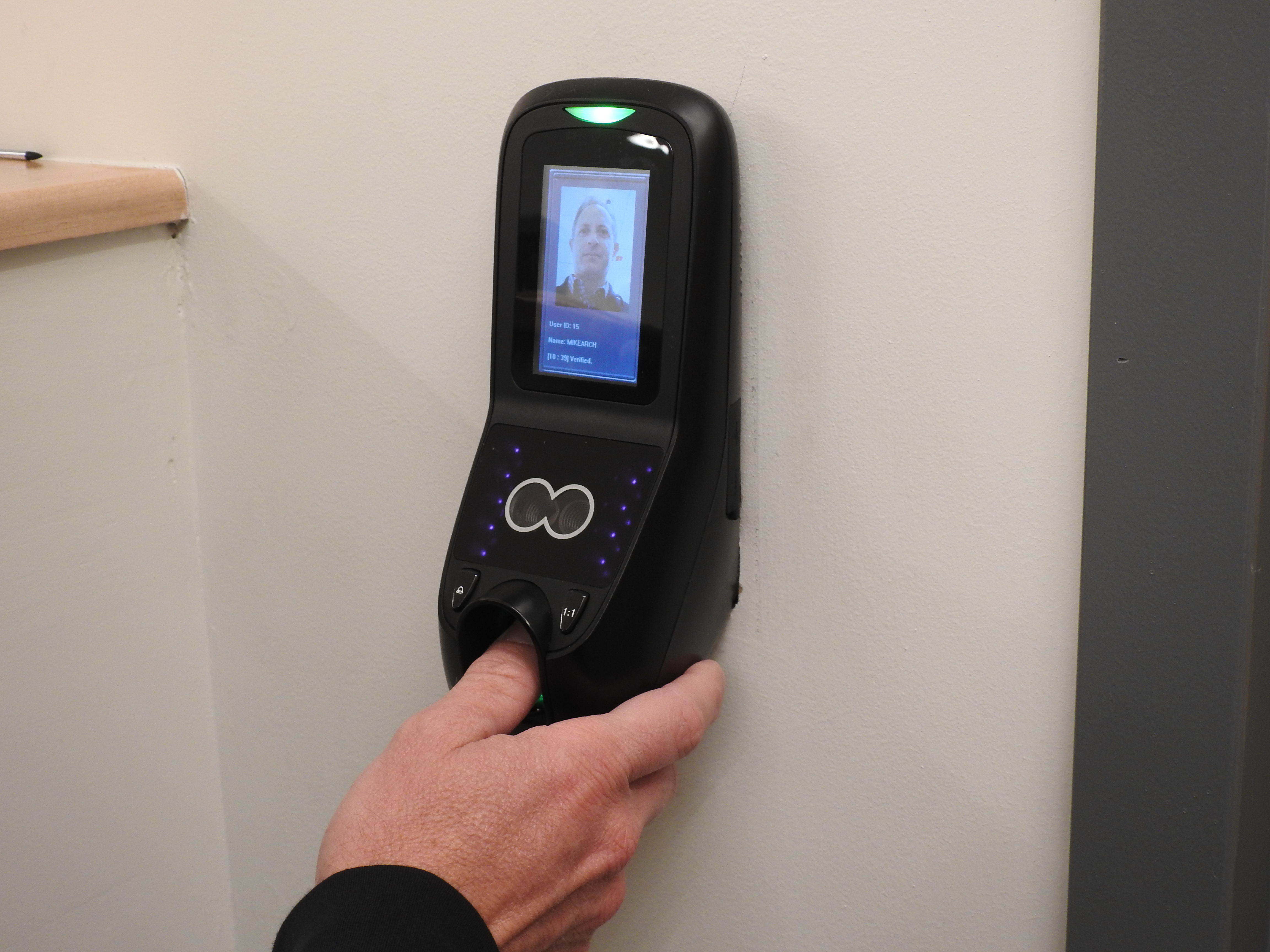 A thumbprint scanner placed on a wall next to a sealed doorway