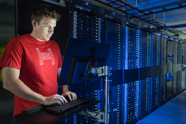 Hivelocity employee working at a computer within a server room