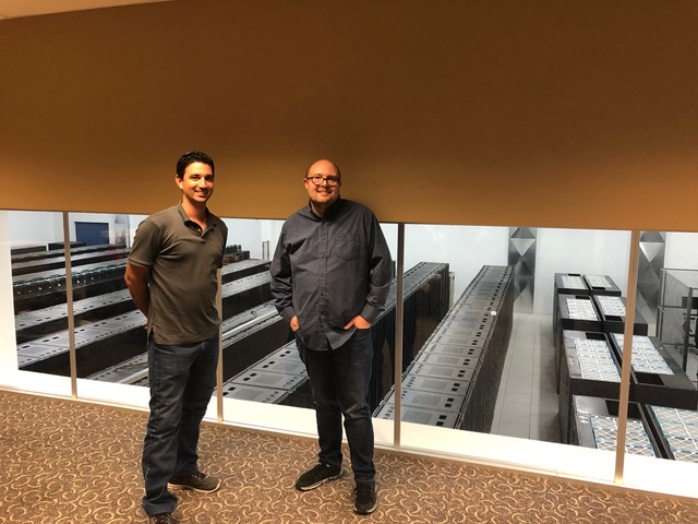 Two men standing outside a room full of server cabinets