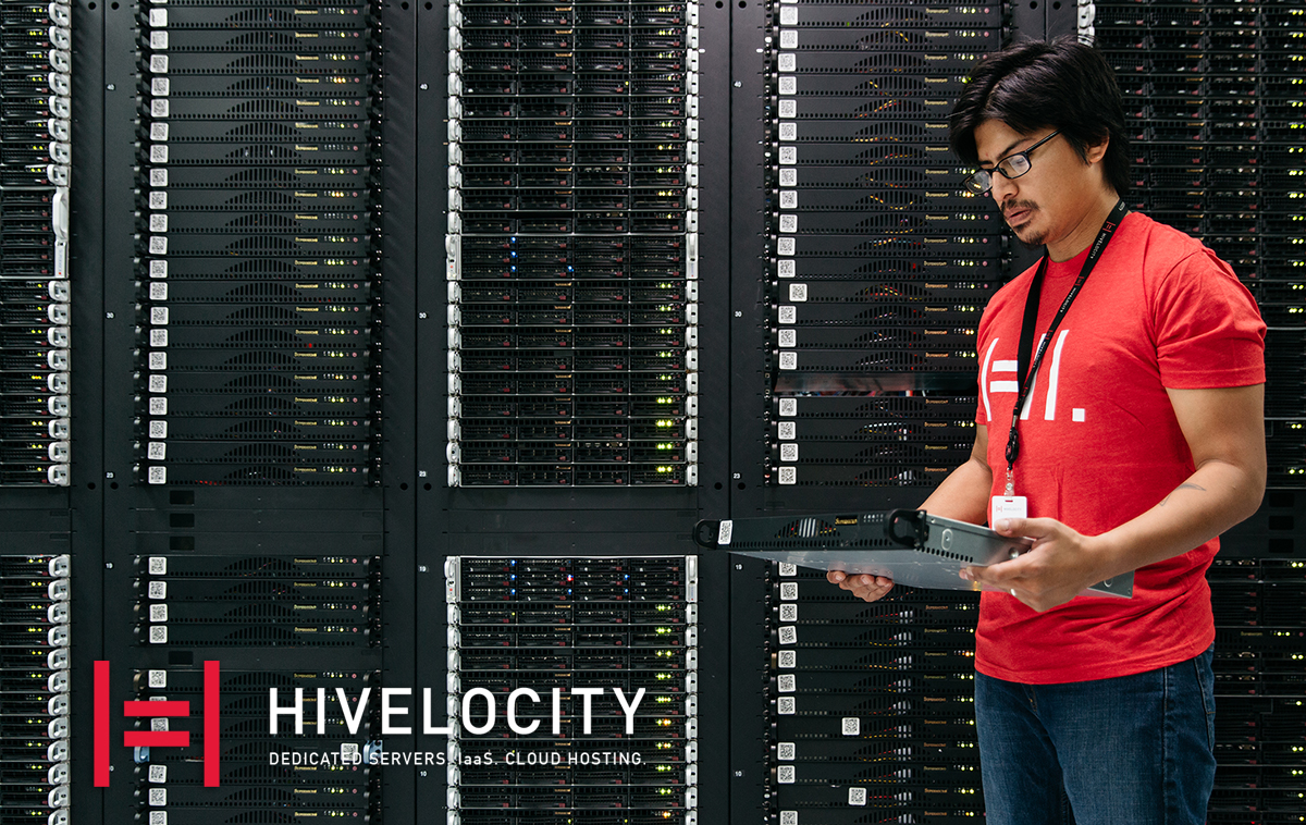 Hivelocity logo on an image of a man holding a server in front of several server cabinets