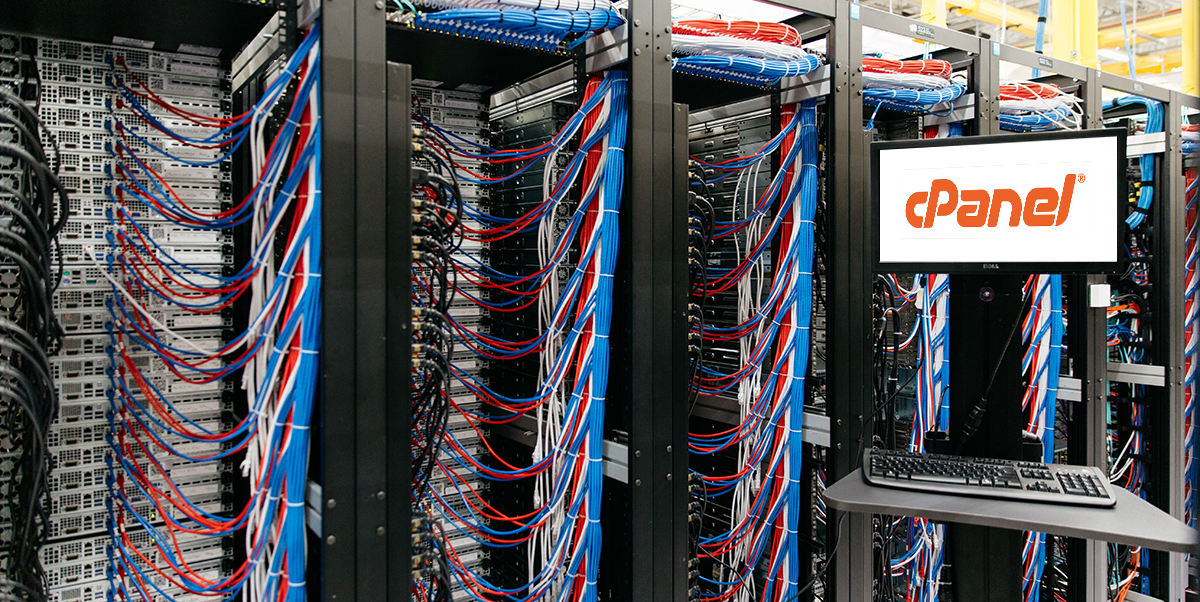 Server cabinets and cables next to computer screen featuring cPanel logo