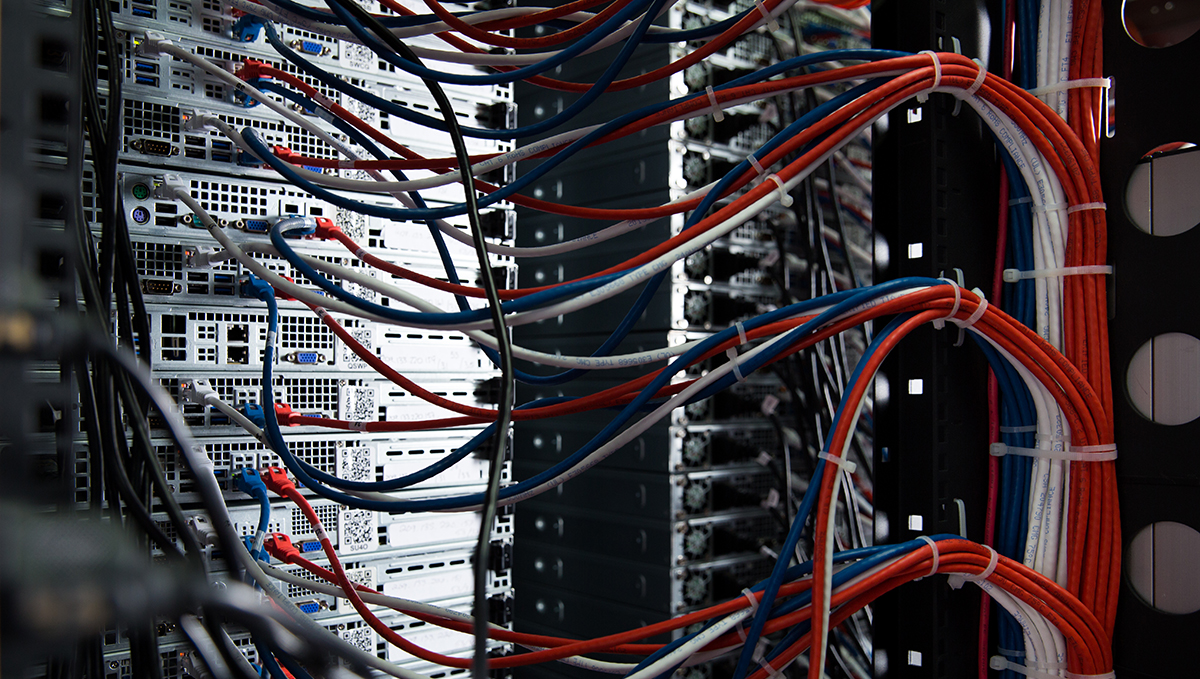Back end of server stack, showing various cables being interwoven together