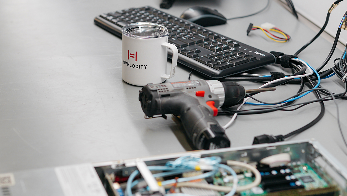 A server being build sitting next to a coffee mug featuring the Hivelocity logo