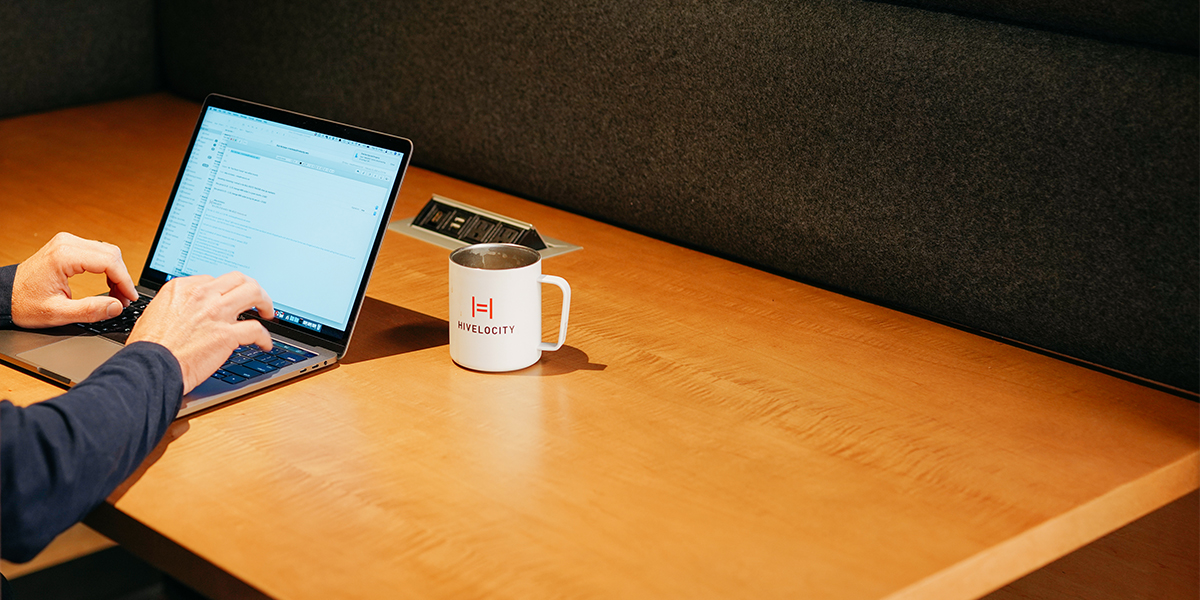Image of a laptop sitting next to a coffee cup featuring the Hivelocity logo